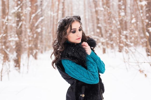 冬の時間に歩く幸せな若い女性。