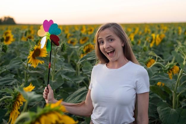 風車のおもちゃでひまわり畑を歩く幸せな若い女性。グリーンエネルギーの概念。