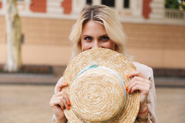 目を覆っている手に帽子を持って屋外で歩く幸せな若い女性