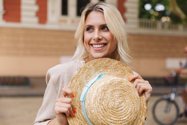 帽子を手に持って屋外を歩く幸せな若い女性