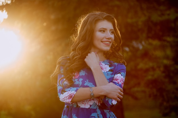 Happy young woman walking in a summer park against sunset