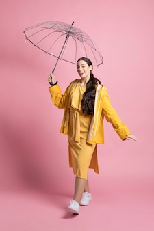 Happy young woman walking while holding an umbrella