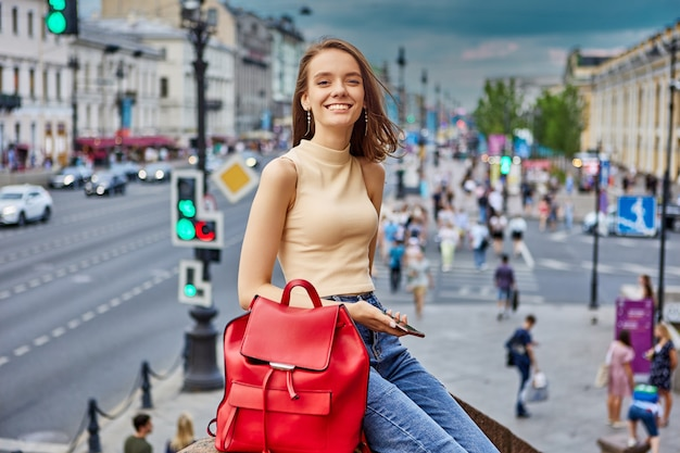Happy young woman walks on city street and smiles