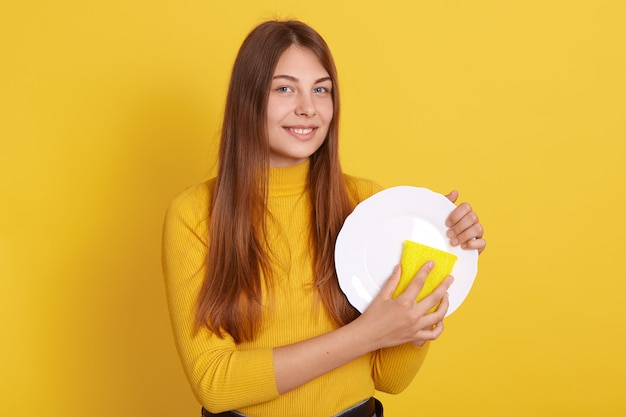 Happy young woman washing dishes, posing isolated on yellow