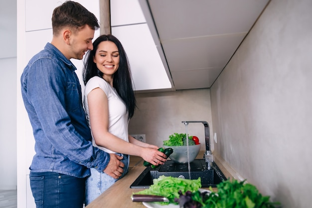 Happy young woman washing vegetables in the sink and handsome man standing next to her