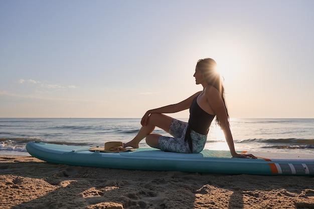 Счастливая молодая женщина, наблюдая восход солнца, сидя на доске с веслом на пляже