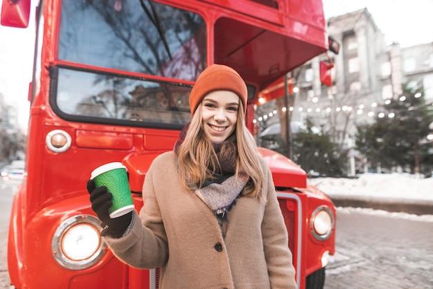帽子と暖かい服を着て幸せな若い女が一杯のコーヒーを手に赤いバスの背景に立って、カメラと笑顔を見てください。