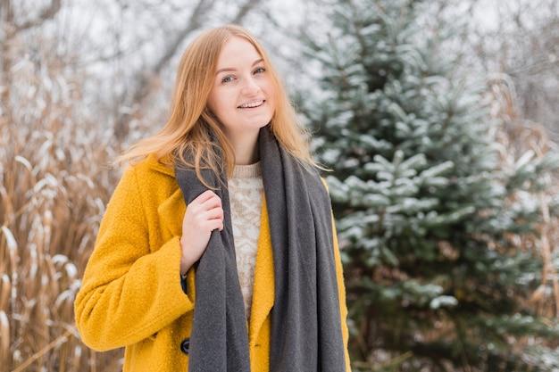 자연 배경 위에 웃고있는 코트와 스카프, 2021 년의 트렌디 한 색상을 입고 행복 한 젊은 여자-노란색과 궁극적 인 회색 조명, 겨울철