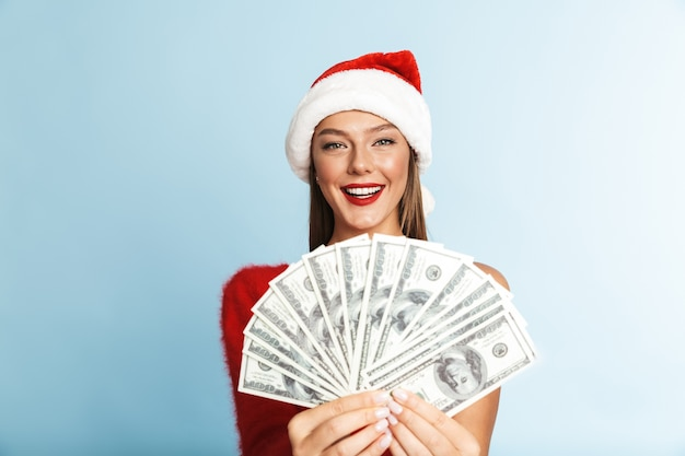 Happy young woman wearing christmas hat, holding money.