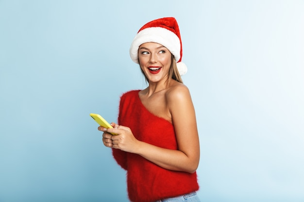 Happy young woman wearing christmas hat, using mobile phone.