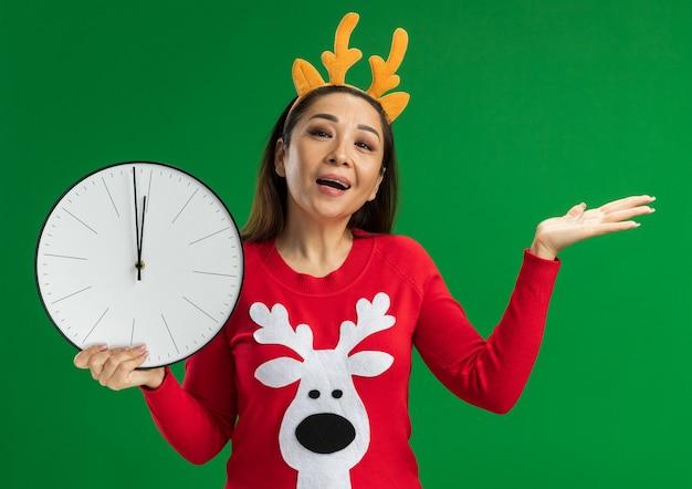 鹿の角と赤いセーターを身に着けている幸せな若い女性は、緑の背景の上に立っている手の腕を提示してカメラの笑顔を見て壁時計を保持しています