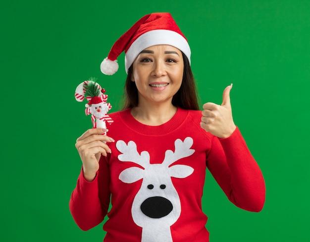 Счастливая молодая женщина в рождественской шляпе санта-клауса и красном свитере держит рождественскую конфету, глядя в камеру, улыбаясь, показывая пальцы вверх, стоя на зеленом фоне