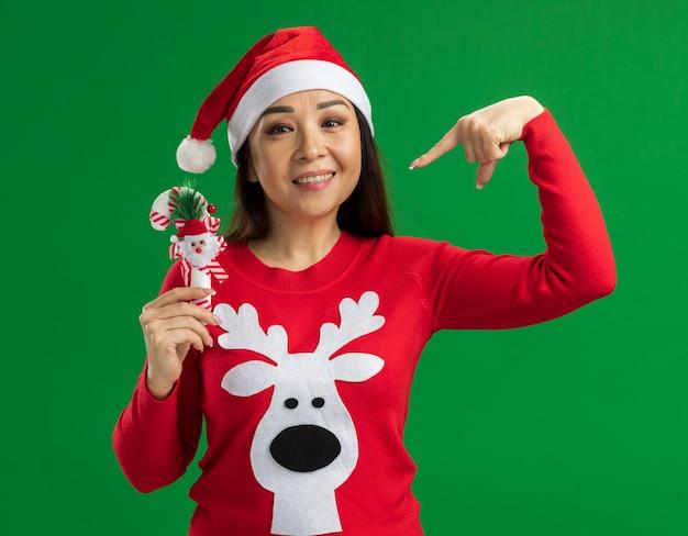Счастливая молодая женщина в рождественской шляпе санта-клауса и красном свитере держит рождественскую конфету, указывая на нее указательным пальцем, улыбаясь, стоя на зеленом фоне