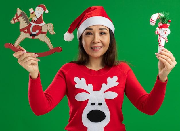 크리스마스 산타 모자와 녹색 배경 위에 서있는 얼굴에 미소로 카메라를 찾고 크리스마스 장난감을 들고 빨간 스웨터를 입고 행복 한 젊은 여자
