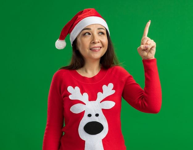 Счастливая молодая женщина в рождественской шляпе санта-клауса и красном свитере смотрит вверх, указывая указательным пальцем, имея новую идею, стоящую на зеленом фоне