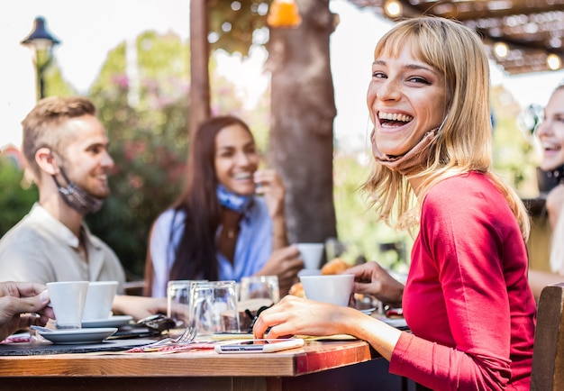 レストランでフェイスマスクを着て幸せな若い女。バーに座ってコーヒーを飲む友人のグループ。