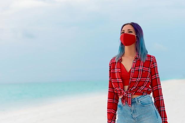 海の旅のコンセプトの近くのビーチで顔保護マスクを身に着けている幸せな若い女性