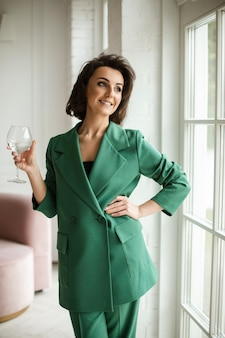 Happy young woman wearing a green costume standing by the window with a glass of water and smiling. style and fashion concept