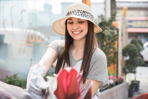 Happy young woman wearing hat taking car of plant