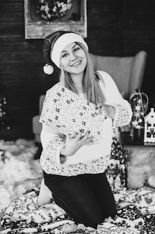 떨어지는 눈으로 장식 된 거실에 서있는 빨간 산타 모자를 쓰고 행복 한 젊은 여자