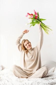 チューリップの花束を持って楽しんでベッドの上で踊るパジャマを着て幸せな若い女性