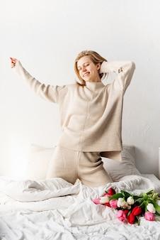 楽しんでベッドの上で踊るパジャマを着て幸せな若い女性
