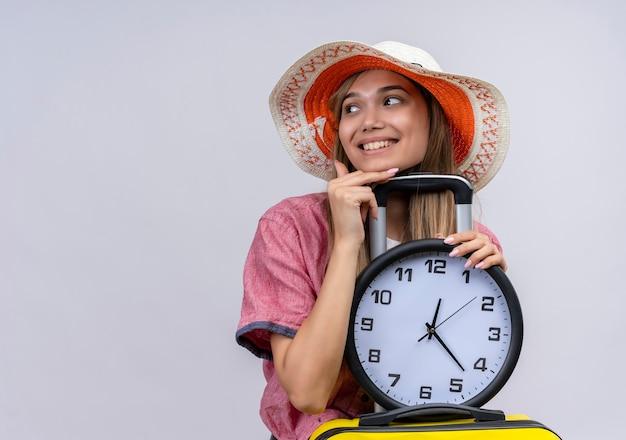 Una giovane donna felice che indossa la camicia rossa che tiene la valigia gialla con l'orologio di parete mentre osserva il lato su una parete bianca