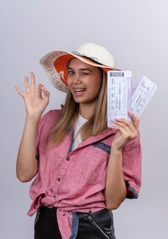 A happy young woman wearing red shirt and sun hat showing plane tickets with ok gesture on a white wall