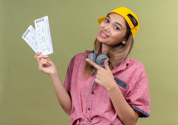 Una giovane donna felice che indossa la camicia rossa e il cappello da baseball giallo con le cuffie che indicano i biglietti aerei con il dito indice su una parete verde