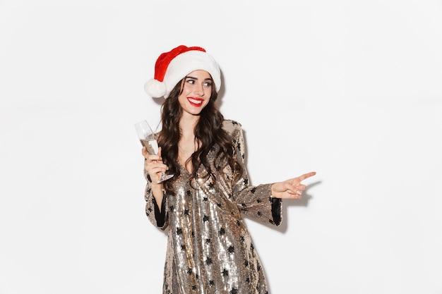 샴페인 잔을 들고 반짝이 드레스와 새 해를 축하하는 산타 모자를 쓰고 행복 한 젊은 여자 화이트 이상 격리
