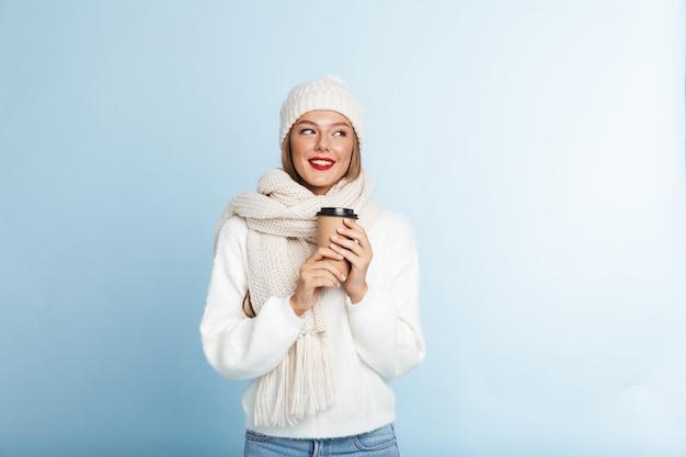 Счастливая молодая женщина в свитере и шляпе, держа кофе на вынос