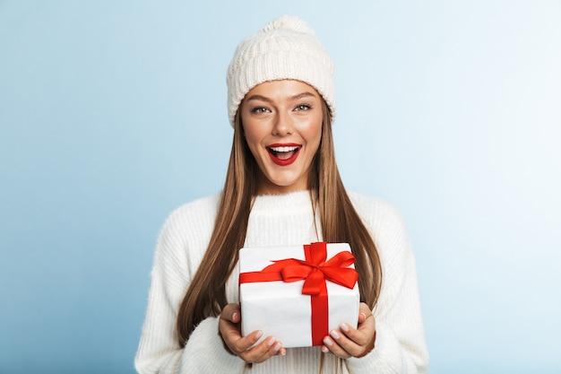 Счастливая молодая женщина в свитере, держащая подарочную коробку