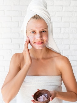 Happy young woman wearing white bath towels on head doing spa procedures applying facial scrub