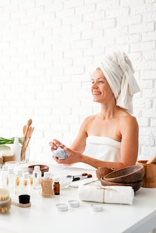 Happy young woman wearing white bathrobes towels on head doing spa procedures mixing natural ingredients in spa beauty salon