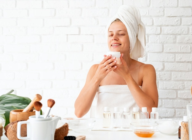 Happy young woman wearing white bathrobes towels on head doing spa procedures in spa beauty salon