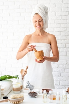스파 뷰티 살롱에서 천연 재료를 혼합하는 스파 절차를 하 고 머리에 흰색 목욕 가운 수건을 입고 행복 한 젊은 여자