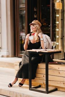 幸せな若い女性は、流行の黒い靴と長いドレスを着て、ハードな一日の後にリラックスしてコーヒーを飲みます。何かを祝うために友人を待っている茶色の帽子とコートの笑顔の女の子の屋外の肖像画。