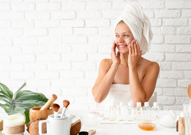 Happy young woman in white bath towels applying face cream doing spa procedures