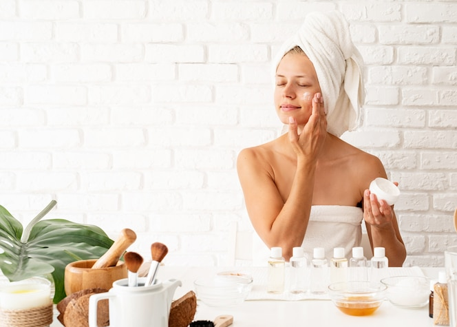 Happy young woman in white bathtowels applying creme on her face skin doing spa precedures