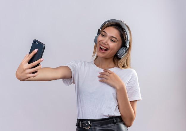 Una giovane donna felice in maglietta bianca che indossa le cuffie prendendo un selfie con lo smartphone su un muro bianco