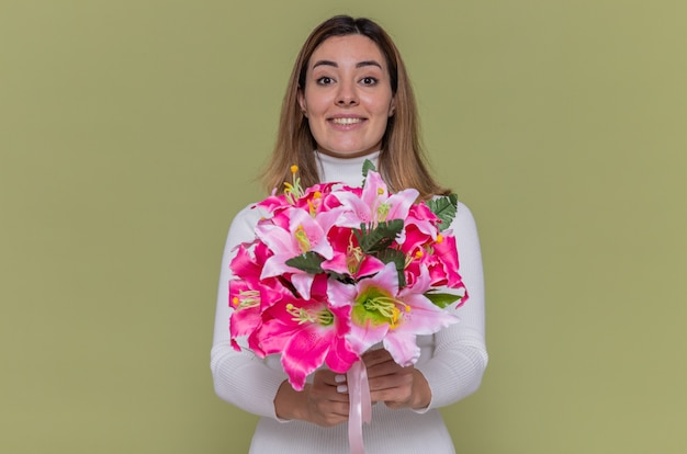 Happy young woman in white turtleneck holding bouquet of flowers looking at front smiling cheerfully celebrating international women's day standing over green wall