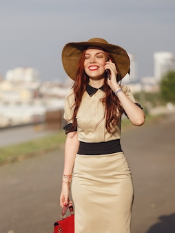 A happy young woman in a wide-brimmed hat is walking in the park in the summer with a bag and talking on the phone