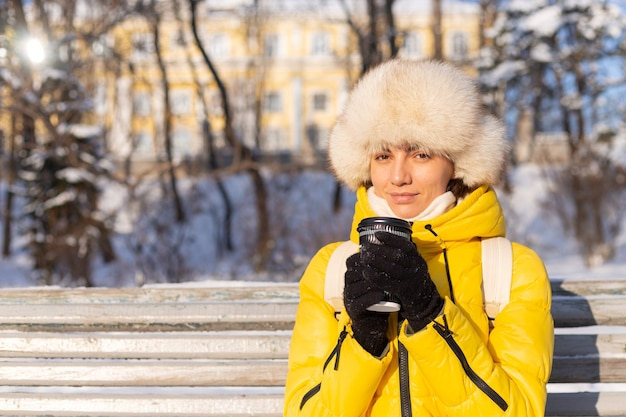 Happy young woman in winter in warm clothes in a snowy park on a sunny day sits on the benches and enjoys the fresh air and coffee alone