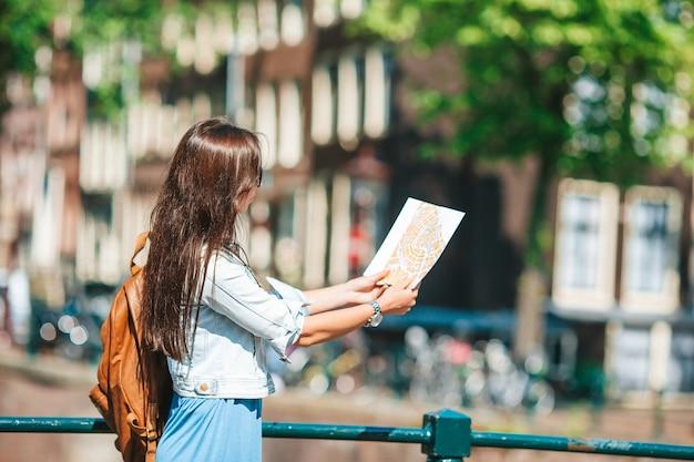 自転車に乗って笑顔の都市地図と幸せな若い女性