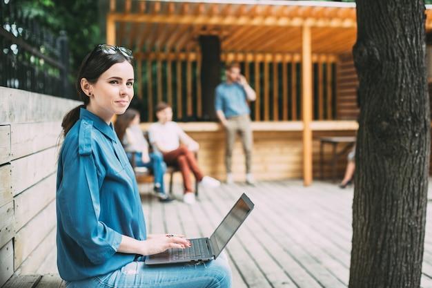Счастливая молодая женщина с ноутбуком на открытом воздухе