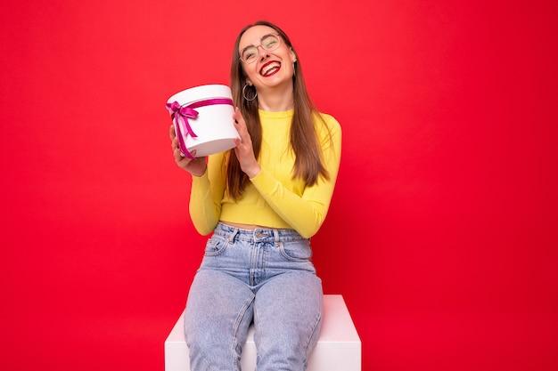 Счастливая молодая женщина с белой подарочной коробкой на красном фоне