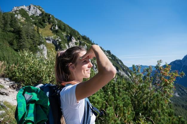 高山を渡る彼女のハイキングで休憩しながら遠くを見ている彼女の背中にバックパックを持つ幸せな若い女性