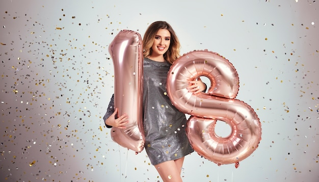 그녀의 생일을 축 하하는 풍선과 함께 행복 한 젊은 여자