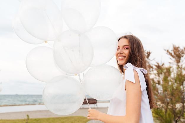 遊歩道を歩いて笑う風船と幸せな若い女性