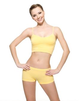 Счастливая молодая женщина с красивым стройным телом в желтой спортивной одежде - изолированная на белой стене